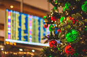 An unrecognizable airport location with a decorated Christmas Tree in the foreground an a flight departures display visible in the background