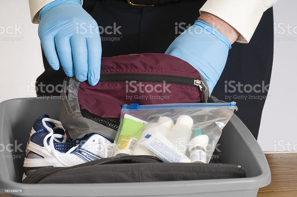 """Airport Security Baggage Search """"Gloved hands of an airport security person examining the contents of a bin with a traveler's fanny pack, shoes, sweater, and allowable liquids.Click below for others in this series and all my airport related images:"""" Airport Stock Photo"""