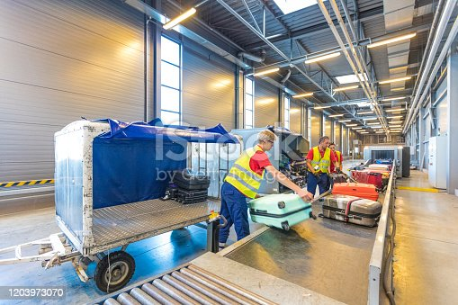Indoor shot of young men unloading luggage from airport baggage trailer. Airport ground crew at work.