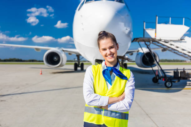 Airport service young woman in front of airplane stock photo