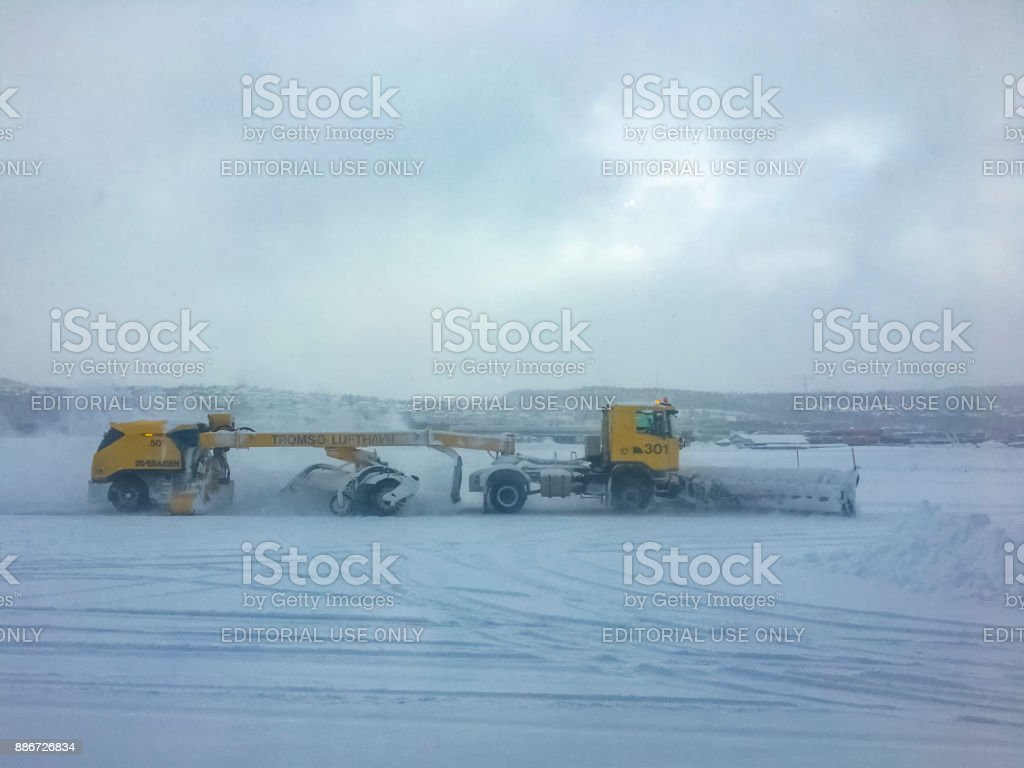 Airport snow plow removing snow and ice from the runwway at Tromso airport stock photo