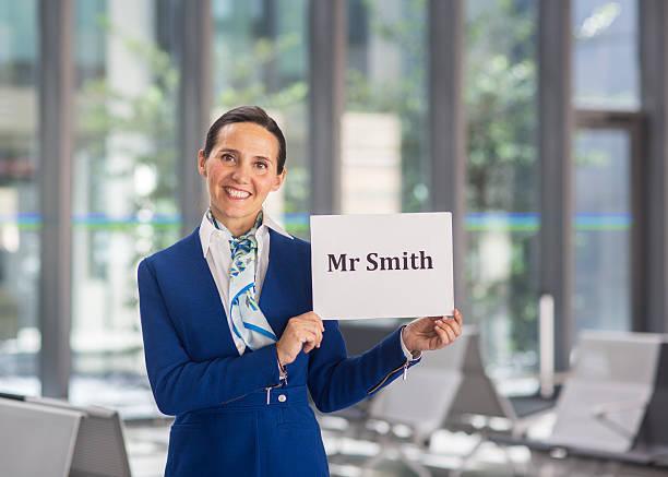 Airport stewardess to welcome Mr Smith - foto de stock