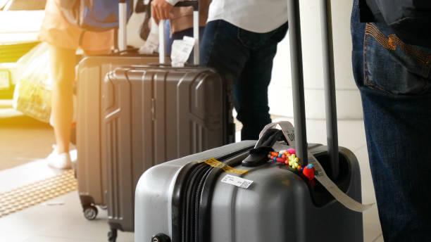 luchthaventaxi. passagier met grote roller bagage staande op de lijn wachten taxi wachtrij bij taxi parkeerplaats bij luchthaven aankomst terminal - airport pickup stockfoto's en -beelden