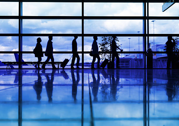 Airport terminal, travellers in silhouette stock photo