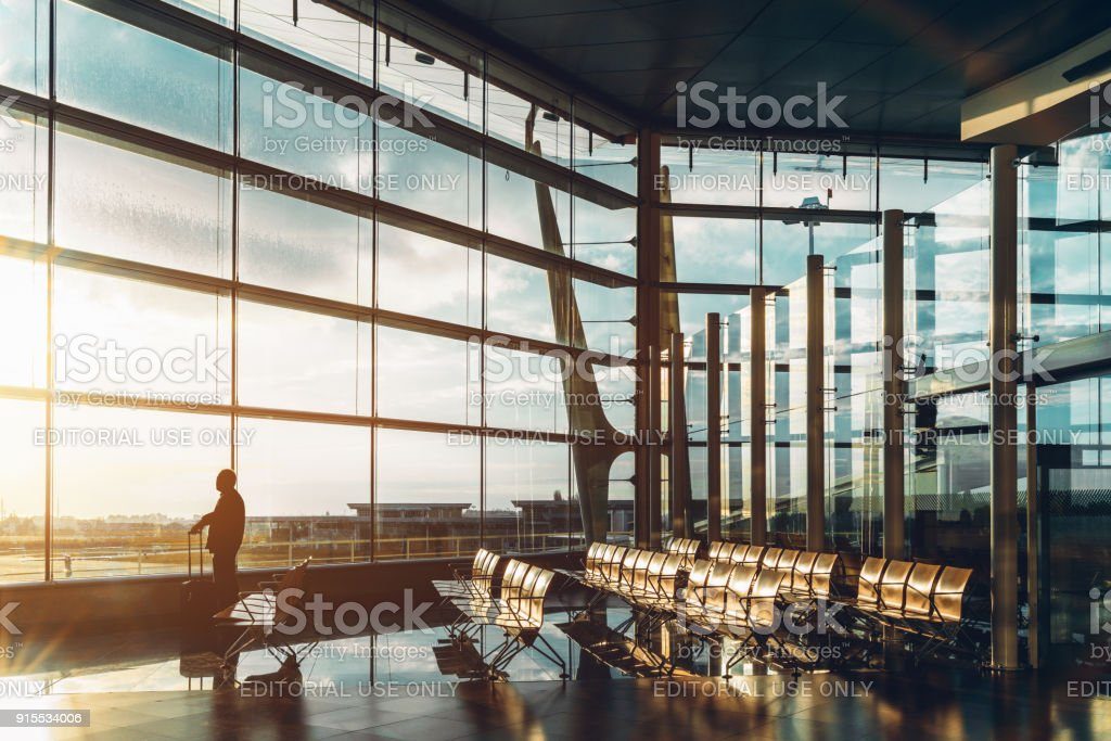 Airport terminal with silhouette of male tourist stock photo