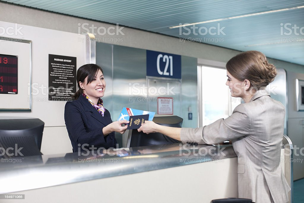 Airport Ticket Counter, Attendant Handing Customer Her Passport stock photo