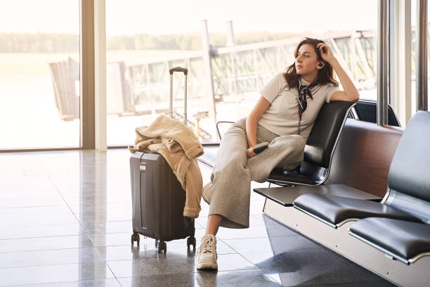 Airport travel lifestyle. Young Gen Z girl traveler sitting in terminal hall with her luggage, trolley bag, passport, smartphone and ticket while waiting for her flight before departure. stock photo
