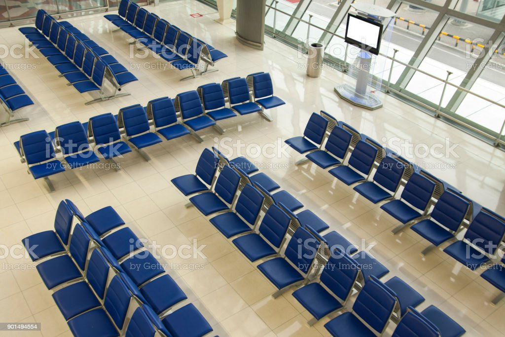 Airport waiting area,lounge,bright and airy with rows of blue seats. stock photo