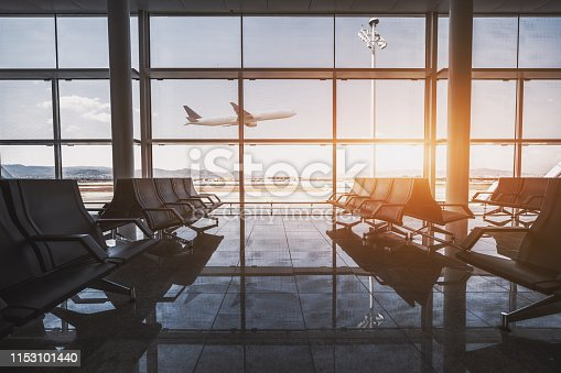 Wide-angle view of a modern aircraft gaining the altitude outside the glass window facade of a contemporary waiting hall with multiple rows of seats and reflections indoors of an airport terminal El Prat in Barcelona