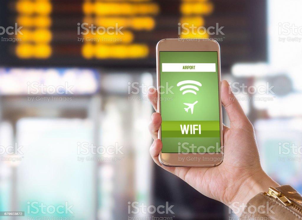 Wifi de l'aéroport. Connexion internet sans fil dans le terminal. Navigation web et mise en ligne avant le vol. Femme tenant le téléphone intelligent dans la main. Calendrier et horaire dans l'arrière-plan flou. - Photo