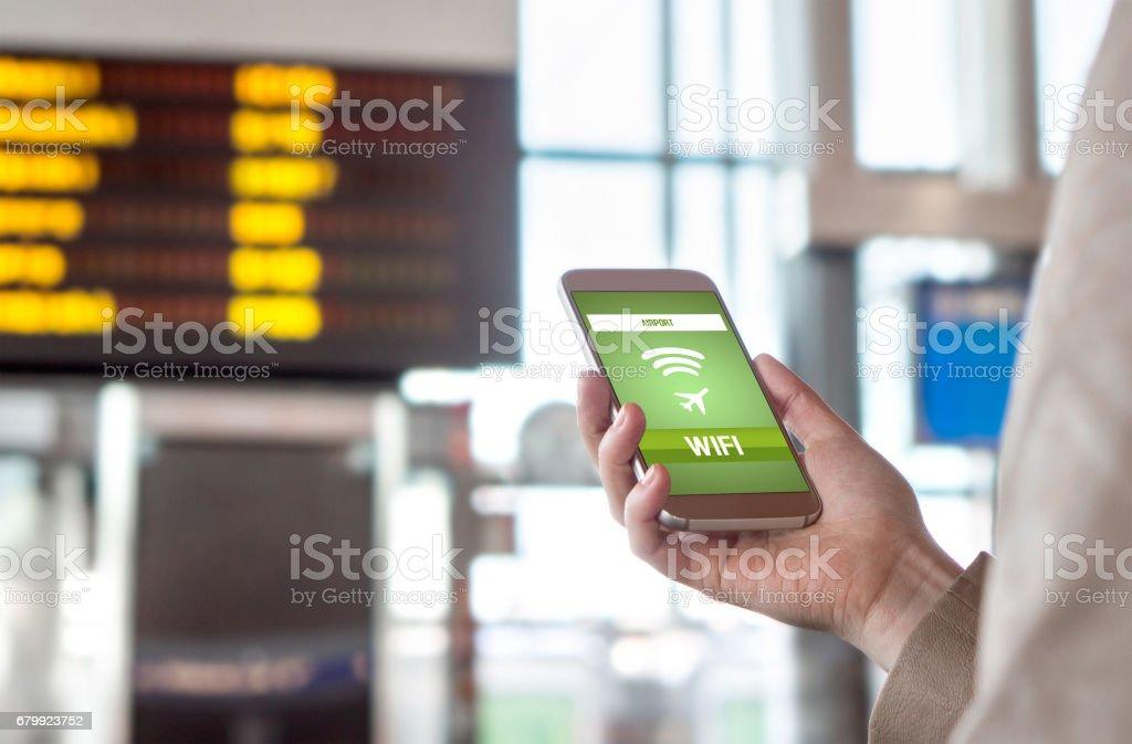Wifi de l'aéroport. Connexion internet sans fil dans le terminal. Femme, navigation web et la mise en ligne avant le départ. Main tenant téléphone mobile. Calendrier et horaire dans l'arrière-plan flou. - Photo