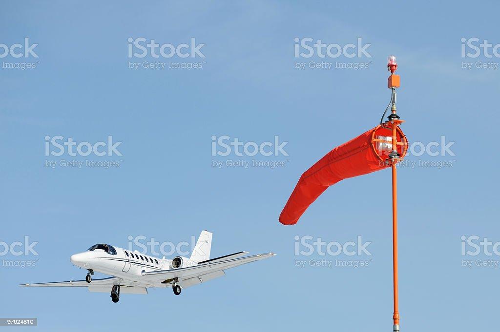 Airport Windsock and a Landing Business Jet royaltyfri bildbanksbilder