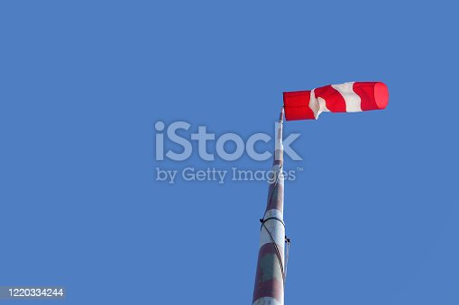 Airport windsock on clear blue sky background in windy weather indicate the local wind direction. at airfield for flying aircraft pilot direction information
