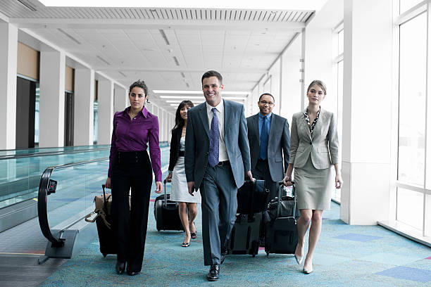 Airport with Business Team Coworkers Walking, Pulling Luggage stock photo