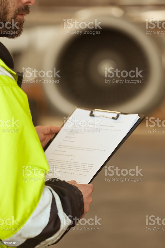 Airport worker checking list in front of jet engine Airport worker holding clipboard in hands standing outdoor in front of airplane engine. Part of, unrecognizable person. Adult Stock Photo