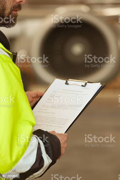 Airport Worker Checking List In Front Of Jet Engine Stock Photo - Download Image Now