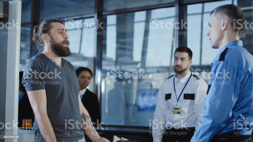 Airport worker checking passenger with metal detector stock photo