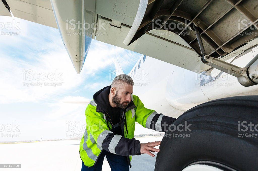 Airport worker checking tires Airport worker chcecking aircraft chassis. Adult Stock Photo