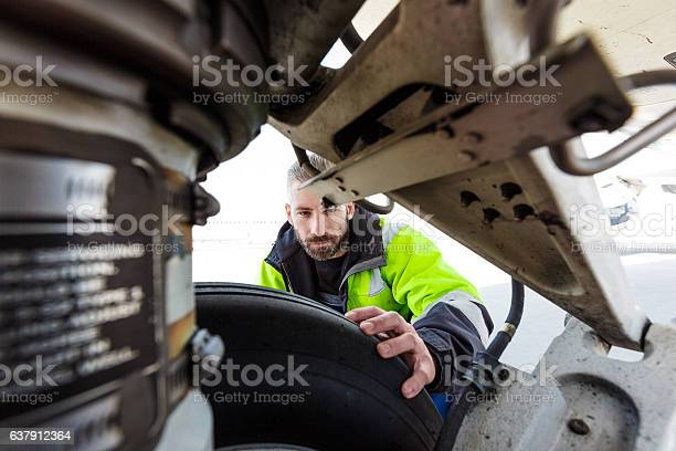 Airport Worker Checking Tires Stock Photo - Download Image Now