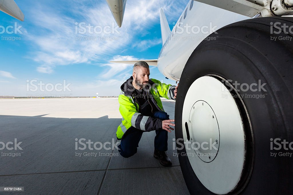 Airport worker checking tires Airport worker chcecking aircraft chassis. Close up. Adult Stock Photo