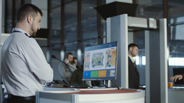 Airport worker exploring x-ray of baggage Man in uniform standing at counter at checking point and watching at monitor with x-ray of luggage. security staff stock pictures, royalty-free photos & images