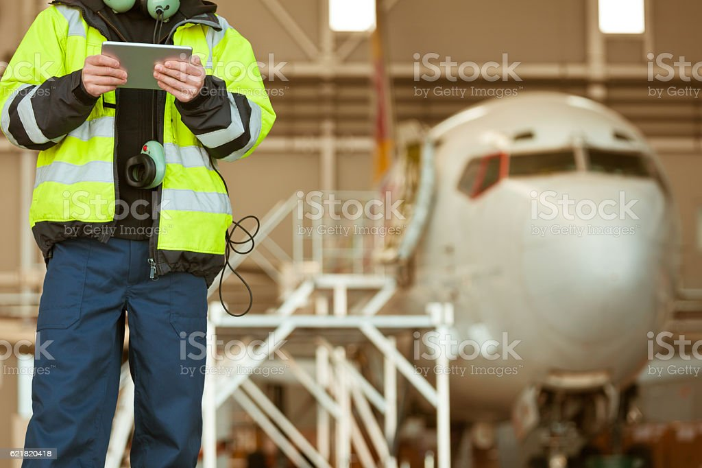 Airport worker in front of aircraft Airport worker using a digital tablet in front of aircraft standing in the hangar. Adult Stock Photo