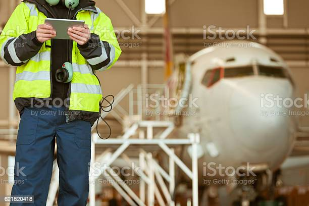 Airport Worker In Front Of Aircraft Stock Photo - Download Image Now