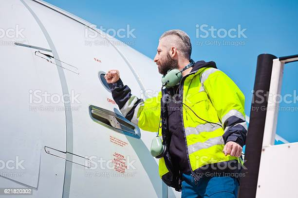 Airport Worker Knocking On The Aircraft Door Stock Photo - Download Image Now