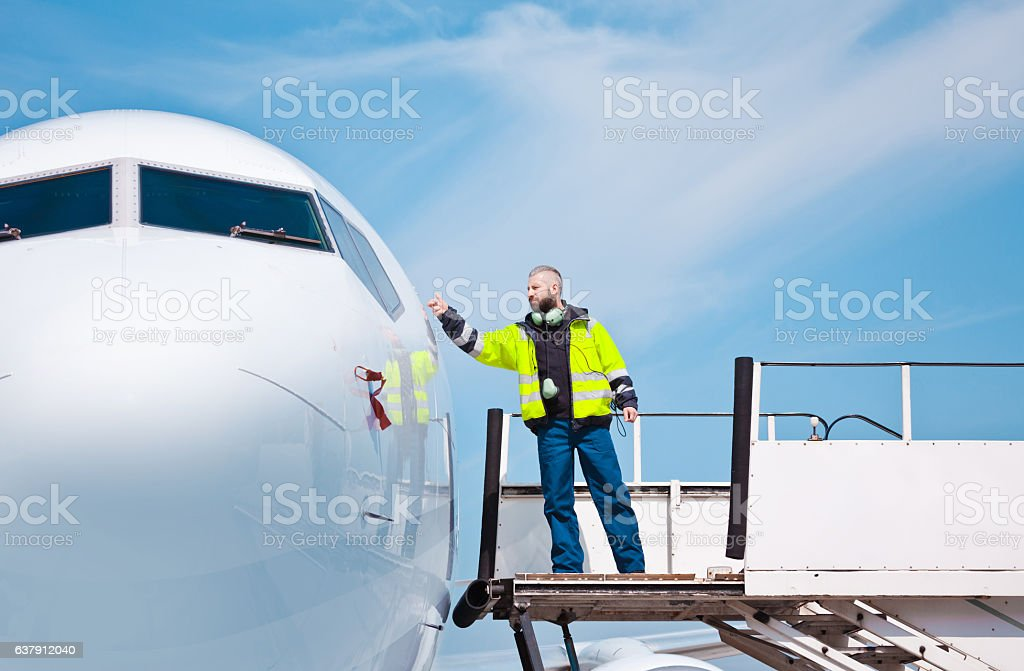 Airport worker knocking on the aircraft door Airport worker knocking on the aircraft door.  Adult Stock Photo
