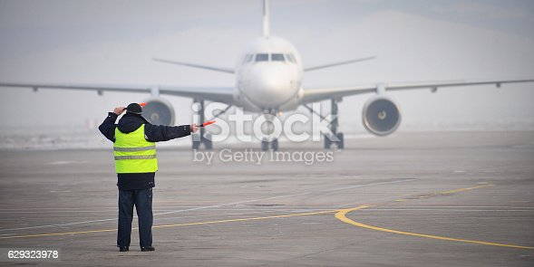 istock airport worker signaling 629323978