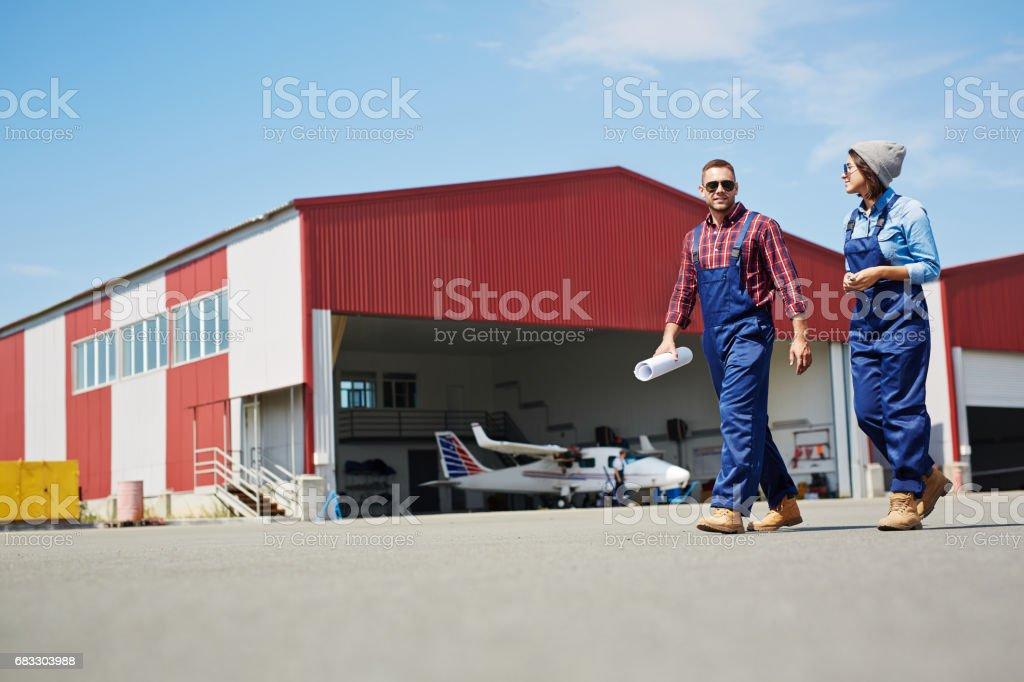 Werknemers van de luchthaven verlaten vlak Hangar royalty free stockfoto