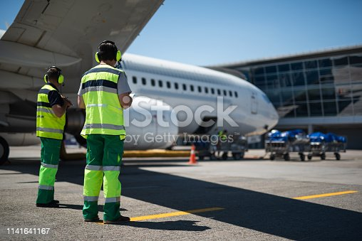 Waiting for the flight. Full length portrait of aviation crewmembers. Passenger airplane and trolleys with luggage on background