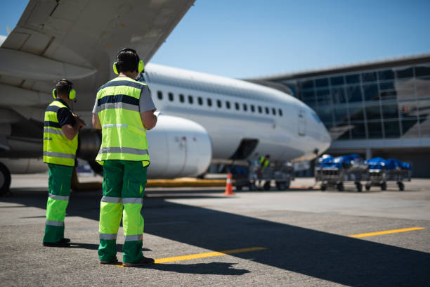 Airport workers looking at modern aircraft Waiting for the flight. Full length portrait of aviation crewmembers. Passenger airplane and trolleys with luggage on background cabin crew stock pictures, royalty-free photos & images
