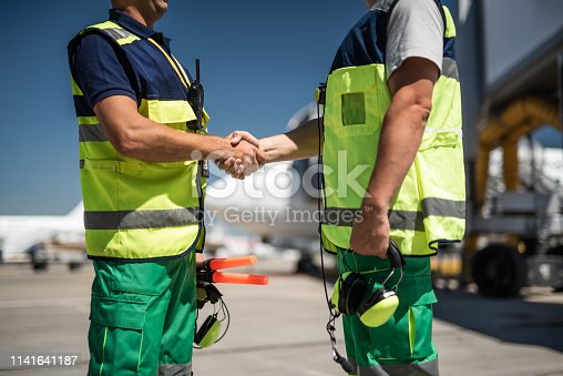 Good to see you. Aviation marshaller greeting colleague. Focus on handshake