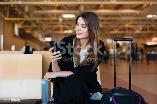 Airport Young female passenger on smart phone at gate waiting in terminal while waiting for her flight. Air travel concept with young casual woman sitting with hand luggage suitcase.