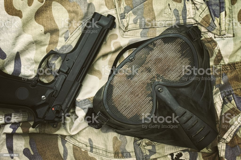 Airsoft protection mask, Terrorist mask and 9mm pistol (M9 Handgun) on camouflage background. stock photo