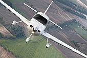 Air to air photo of a modern civil cirrus airplane with propeller flying over the agricultural fields, landing gears down.