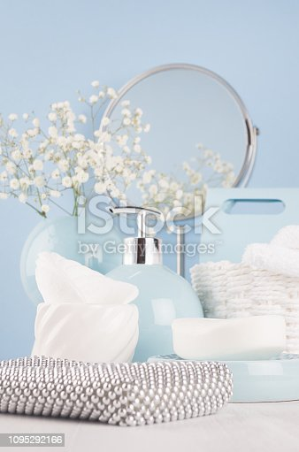 1056636898 istock photo Airy blue dressing table with cosmetic accessories, mirror, basket, towel, silver bag, flowers and ceramic bowls on white wood board and pastel blue wall. 1095292166