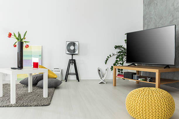 Airy interior for enthusiasts of good movies Modern living room with simple but trendy furniture and a tv set, arranged in grey and yellow magazine rack stock pictures, royalty-free photos & images