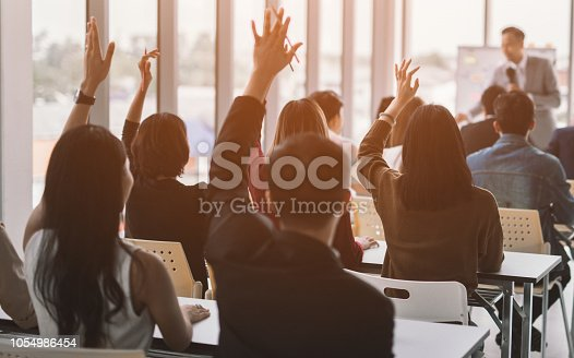istock aised up hands and arms of large group in seminar class room 1054986454