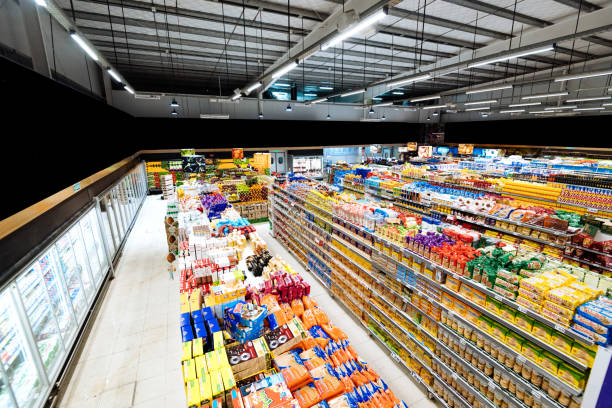 Aisles and shelves in supermarket, wide angle view Shopping in modern supermarket grocery aisle stock pictures, royalty-free photos & images