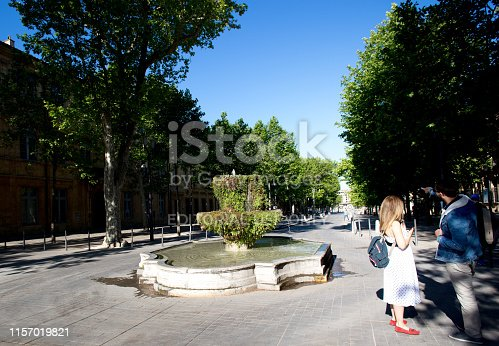 Aix-en-Provence, France: Two people chat in early morning at the Fountain of Nine Canons (Fontaine des Neufs-Canons), built in 1691, on the Cours Mirabeau in Aix-en-Provence.