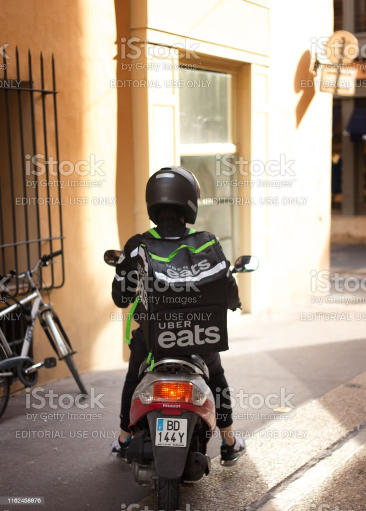 An Uber Eats delivery person on a motorbike in downtown...