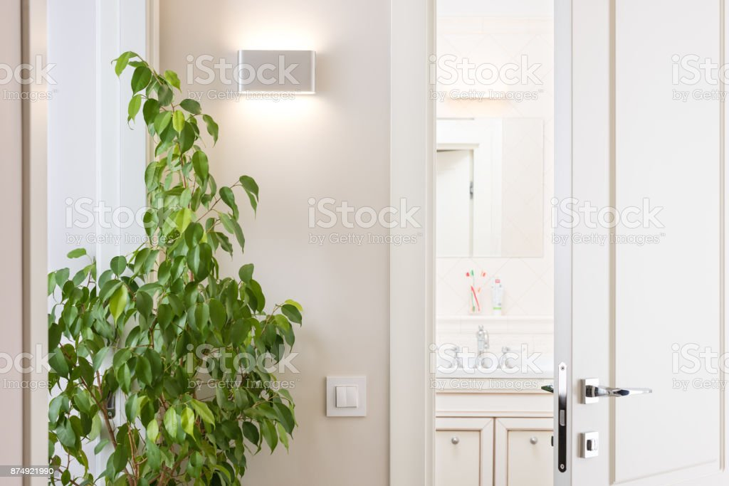 Ajar white door in the bright bathroom. Series switch and modern wall lamp on light gray wall stock photo