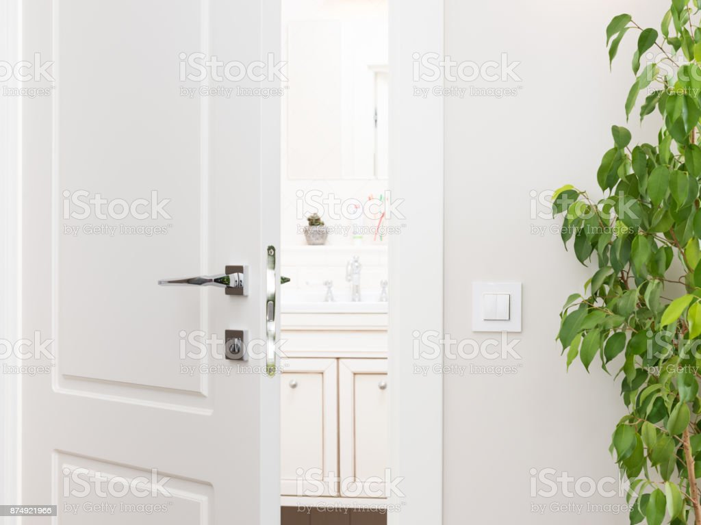 Ajar white door to the bathroom. Series switch on a light gray wall stock photo