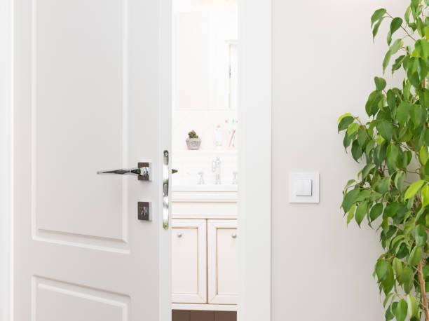 einen spaltbreit weiße tür zum badezimmer. schalterserie auf eine leicht graue wand - schlüssel dekorationen stock-fotos und bilder