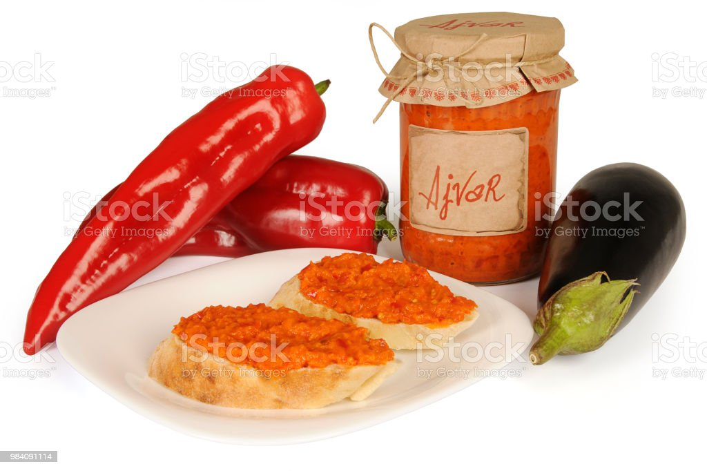 Ajvar, a delicious roasted red pepper and eggplant dish. Serbian and Macedonian traditional dish. Sauce spread on two slices of bread on plate. stock photo