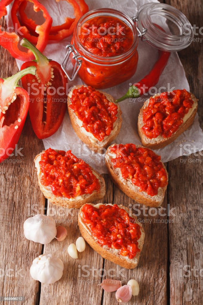 Ajvar - delicious dish of red peppers, onions and garlic closeup. vertical stock photo