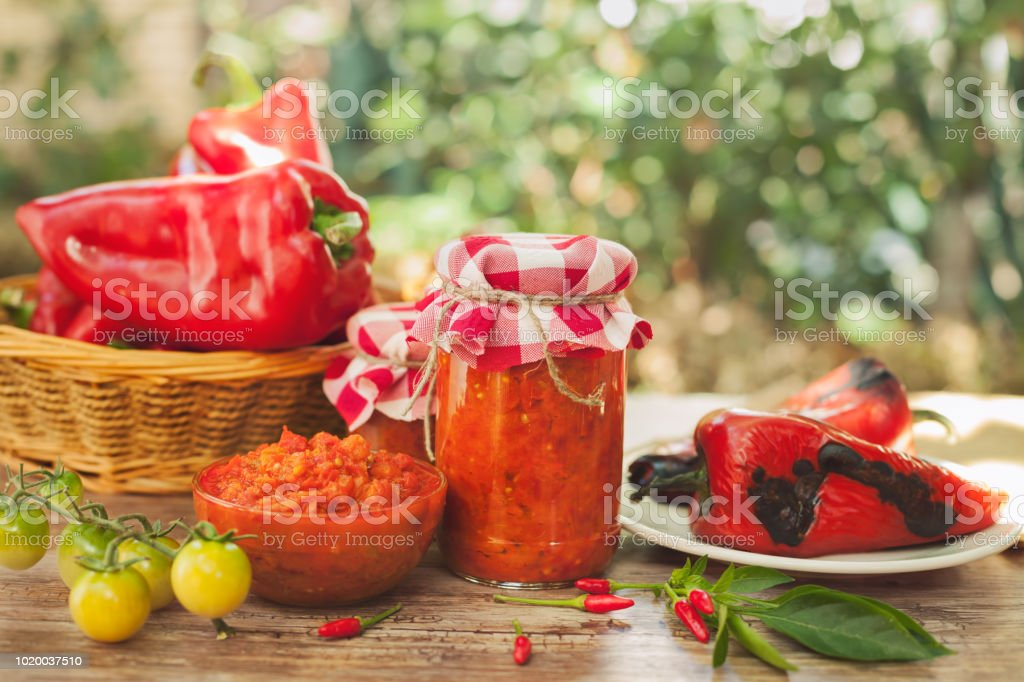 Ajvar in a glass jar and glass bowl stock photo