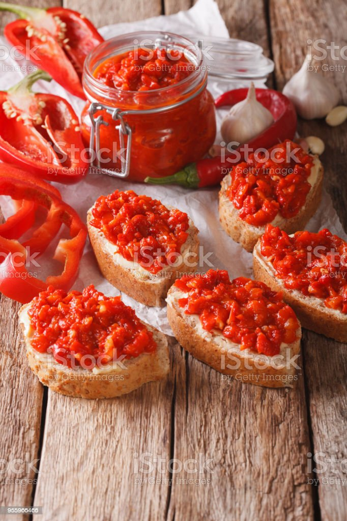 Ajvar in a glass jar and toast on a wooden background. Vertical stock photo